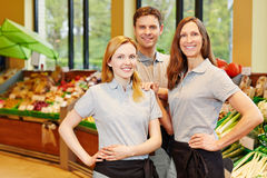 Team in supermarket with store manager and salespeople. Happy team in supermarket with store manager and two salespeople Royalty Free Stock Photos