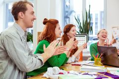 Delighted happy people showing their approval with applause. Team support. Delighted happy people sitting at the desks while showing their approval with applause stock photos