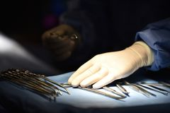 Team surgeon at work in operating room. Surgical light in the operating room. Preparation for the beginning of surgical operation with a cut. The surgeon is Royalty Free Stock Image