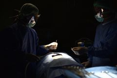 Team surgeon at work in operating room. Surgical light in the operating room. Preparation for the beginning of surgical operation with a cut. The surgeon is Royalty Free Stock Photo