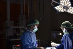 Team surgeon at work in operating room. Surgical light in the operating room. Preparation for the beginning of surgical operation with a cut. The surgeon is Stock Images