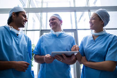 Team of surgeons discussing over digital tablet Royalty Free Stock Photo