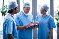 Team of surgeons discussing over medical reports Stock Photos