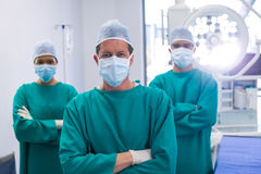 Team of surgeons wearing surgical mask in operation theater. Of hospital Stock Images