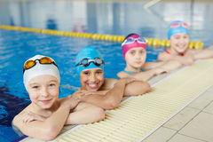 Team of Swimmers at Pool Border. Group of joyful boys and girls smiling to camera at border of swimming pool during practice Royalty Free Stock Image