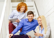 Team with tablet pc computer sitting on staircase Stock Images