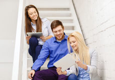 Team with tablet pc computer sitting on staircase Stock Photography