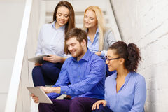 Team with tablet pc computer sitting on staircase Royalty Free Stock Photos