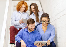 Team with tablet pc computer sitting on staircase Royalty Free Stock Photo