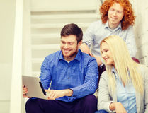 Team with tablet pc computer sitting on staircase Royalty Free Stock Image
