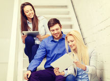 Team with tablet pc computer sitting on staircase Royalty Free Stock Images