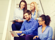 Team with tablet pc computer sitting on staircase Royalty Free Stock Photography