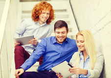 Team with tablet pc computer sitting on staircase Stock Photo