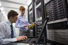 Team of technicians using digital cable analyser on servers Stock Image