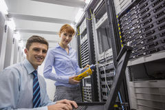 Team of technicians using digital cable analyser on servers Stock Photo