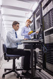Team of technicians using digital cable analyser on servers. In large data center Stock Image