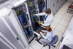 Team of technicians using digital cable analyser on servers. In large data center Royalty Free Stock Photo