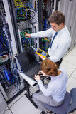 Team of technicians using digital cable analyser on servers. In large data center Stock Images