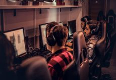 Team of teenage gamers plays in a multiplayer video game on pc in a gaming club. royalty free stock photography