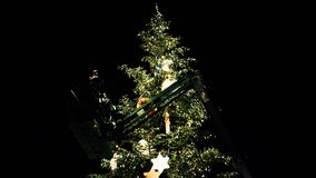 Team in telescopic crane preparing to decorate the Christmas Tree. Unrecognizable workers rising on top of Christmas Tree with telescopic crane in central Place stock video