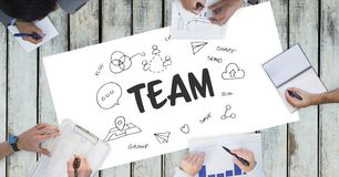 Team text by icons and business people on table. Digital composite of Team text by icons and business people on table Royalty Free Stock Photos