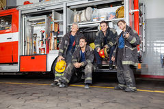Team Of Thoughtful Firefighters By Firetruck Stock Photo