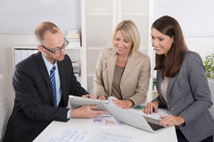 Team of three business people sitting together at desk in a meet Royalty Free Stock Images