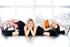 Team of three females posing, sitting in splits in fitness class Stock Images