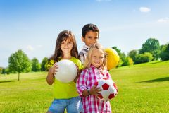 Team of three happy kids with balls royalty free stock photos