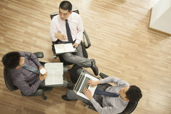 Team of three people working on the project and sitting in a circle, overhead shot Stock Images