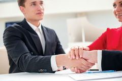 Team. Three successful and confident businesspeople shake hands. Stock Images