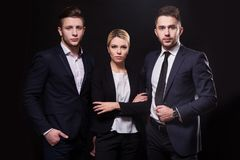 Team of three successful stylish young lawyers on a black backgr Royalty Free Stock Photo