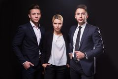 Team of three successful stylish young lawyers on a black backgr Royalty Free Stock Images