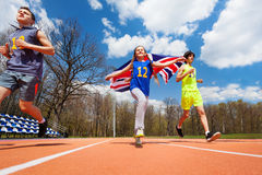 Team of three teenage sprinters with British flag. Team of three teenage sprinters, boys and girl, running with British flag on the track Royalty Free Stock Photos