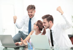 Team of three work colleagues with their arms raised in celebrat Royalty Free Stock Photos