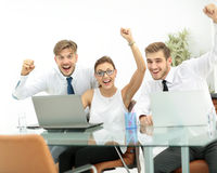 Team of three work colleagues with their arms raised in celebrat Stock Image