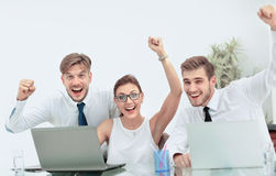 Team of three work colleagues with their arms raised in celebrat Stock Photography