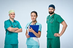 A team of three young doctors. The team included a doctor and a woman, two men doctors. They are dressed in scrubs. Girl standing in front and holds the tablet Stock Image