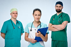 A team of three young doctors. The team included a doctor and a woman, two men doctors. They are dressed in scrubs. On the necks o. A team of three young doctors Royalty Free Stock Images