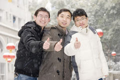 Team  thumbs up in snow. Three young man with coats  smile thumbs up  in snow day in winter Stock Image