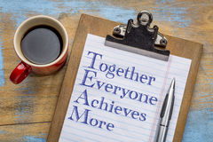 TEAM - together everyone achieves more acronym. TEAM acronym - together everyone achieves more - motivational text on a clipboard with a cup of coffee royalty free stock photos