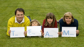 TEAM [Tom, Erica, Anna, Martha]. Parents with kids laying on the grass Royalty Free Stock Photography