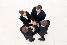We are team. Top view of four business people in formalwear standing close to each other and holding hands together Royalty Free Stock Photo