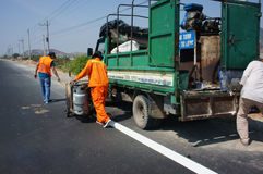 Team of traffice worker work on road. BINH THUAN, VIETNAM- JAN 23: Team of civil worker work on highway, they draw white line on road with eject machine, truck Stock Photos