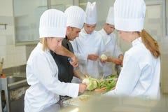 Team trainee chefs preparing vegetables. Team of trainee chefs preparing vegetables Royalty Free Stock Image