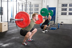 Team trains squats at fitness gym center Royalty Free Stock Image
