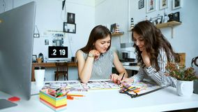 Young female architects discussing with blueprint in office. Team of two female architects, sitting at desk in office with building plans. The women talk and stock footage
