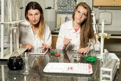 Team of two female laboratory technicians working in chemical or pharmaceutical laboratory. Team of two, Caucasian white, female laboratory technicians in white stock images