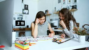 Young female architects discussing with blueprint in office. Team of two woman architects, sitting at desk in office with building plans. The women talk and stock video footage