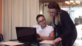 A team of two business girls discussing a business project in the office. A team of two young beautiful business girls in glasses discussing a business project stock video